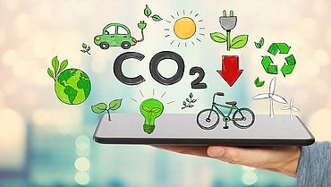 Reduce CO2 with man holding a tablet